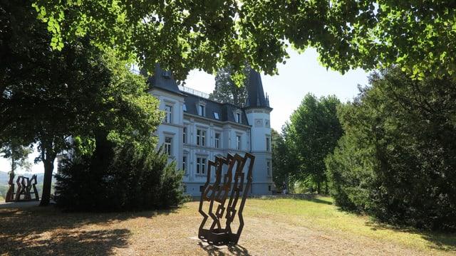 Skulptur aus Eisen auf einem Rasenfeld, dahinter grosse Villa