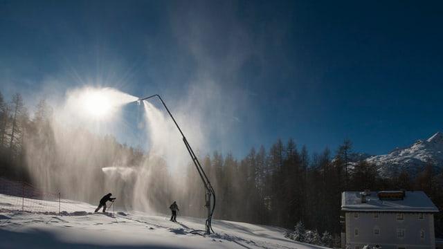Skifahrer passieren in der Nacht eine Beschneiungsanlage in der Region St. Moritz.