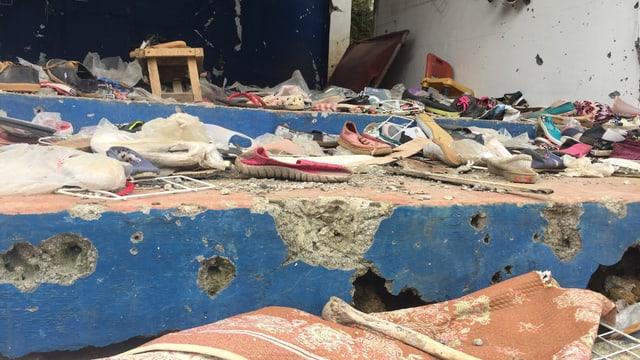 Zerschossener Laden, am Boden liegen Schuhe.
