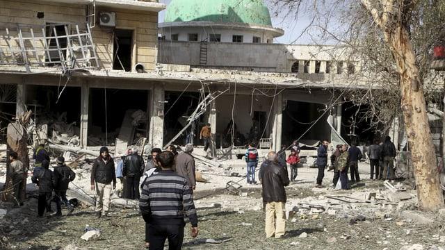 Menschen stehen vor zerbombten Häuser