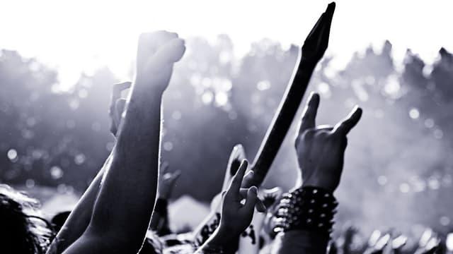 schwarzweiss bild von empor gestreckten metalfan-armen an einem festival