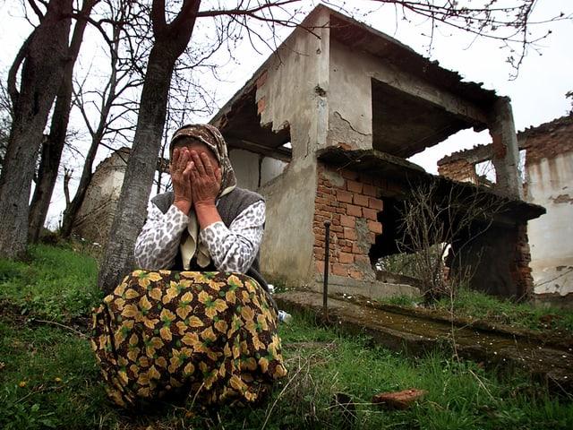 Eine Frau trauert vor ihrem zerstörten Haus.