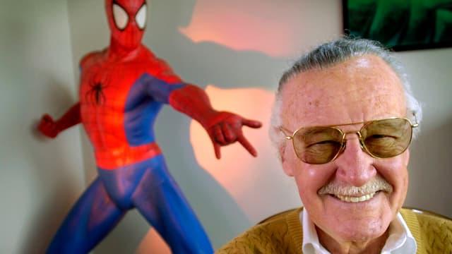 Stan Lee lachend im Bildvordergrund, hinten Spiderman-Puppe