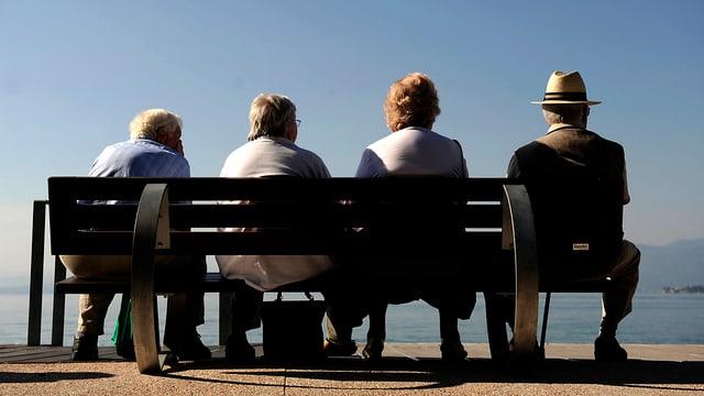 Symbolbild: Vier ältere Personen sitzen auf einer Bank am Seeufer.