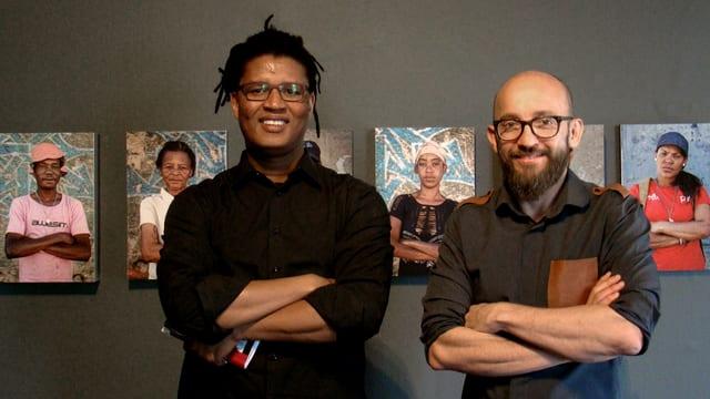 Zwei Männer stehen vor ausgestellten Fotografien.
