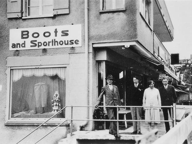 Drei Männer und eine Frau stehen vor einem Geschäft.