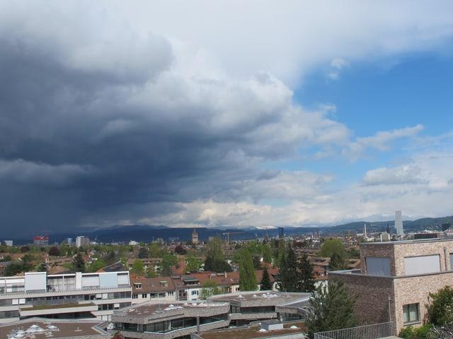 Dunkle Wolken links, rechts blauer Himmel.