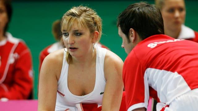 Timea Bacsinszky sitzt auf der Bank, vor ihr kniet Coach Severin Lüthi.