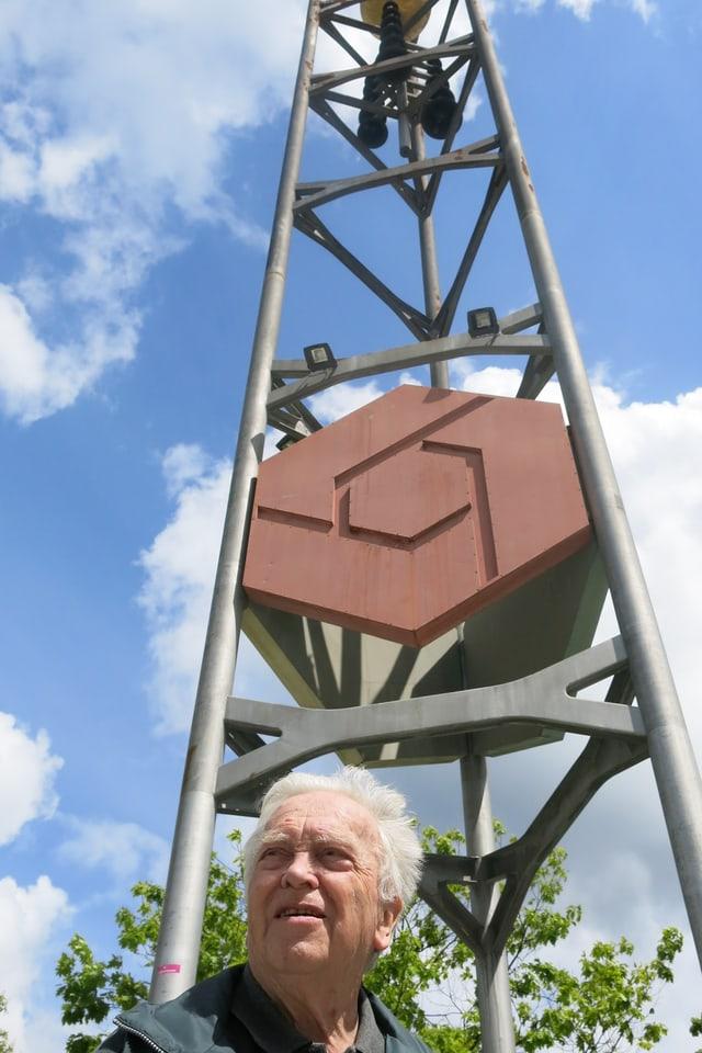 Der 90jährige Ernst Wermuth steht vor einem hohen Turm mit Glocken dran.