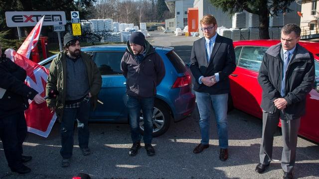 Streikende und Unternehmensvertreter vor zwei Autos im Gespräch