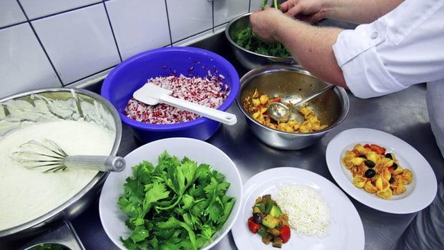 Ein Koch bereitet in der Küche ein Menü zu mit viel Gemüse und Salat.