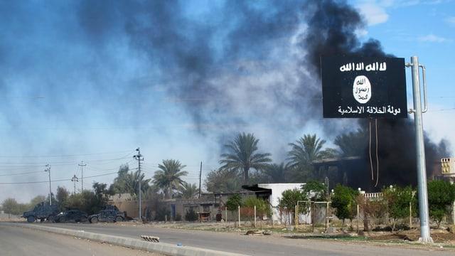 Eine IS-Flagge vor rauchenden Gebäuden.