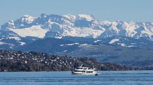 Ein Schiff fährt auf dem tiefblauen Zürichsee, im Hintergrund die weiss-verschneiten Alpen.