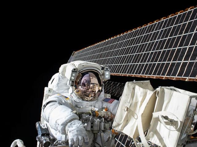 Ein Astronaut auf einer Aussenmission vor den Sonnensegeln der ISS.