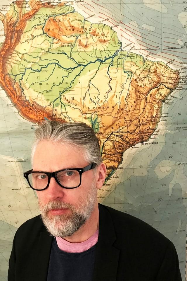 Mann in schwarzem Pullover vor Landkarte Südamerikas