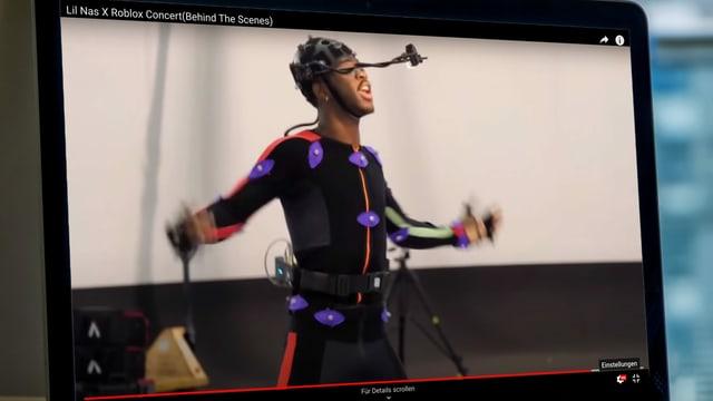ein Laptop, worauf ein Video eines Mannes mit Sensoren und Mikrofon ist