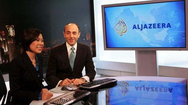 Eine Moderatorin und ein Moderator vor einem Bildschirm mit «Al Jazeera»-Logo.
