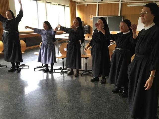 Nonnen stehen in einem Halbkreis und singen.