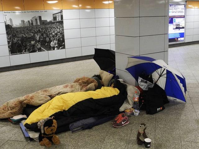 Zwei Personen in Schlafsäcken liegen in einer Unterführung.