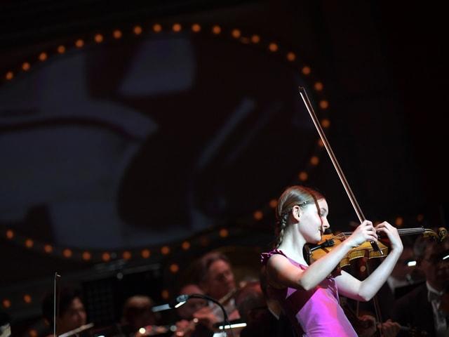 Ein Mädchen mit der Geige auf einer Bühne.