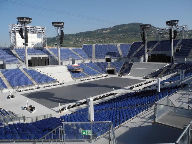 Blick über die gigantische Arena mit blauen Sitzen.