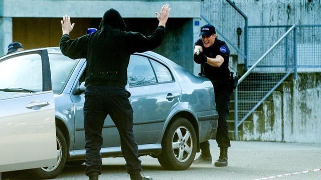 Ein Polizist hinter einem Auto zielt auf einen Mann mit erhobenen Armen.