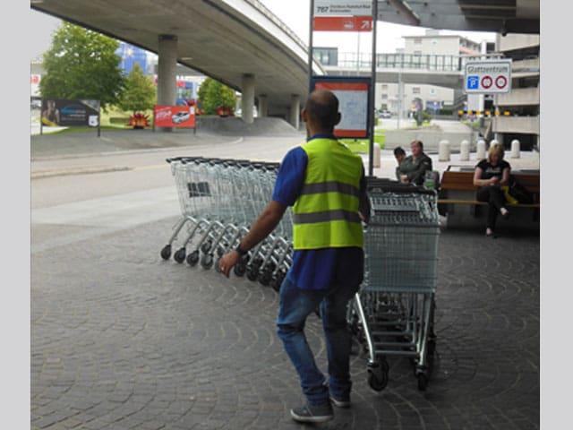 Ein Mann zieht eine Reihe ineinnader verschachtelte Einkaufswagen.