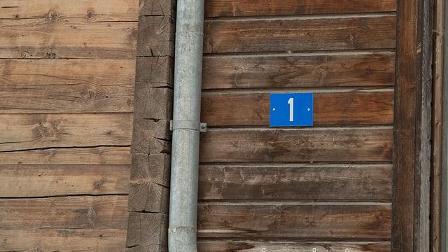 Ina tabla cun la numera da la chasa.