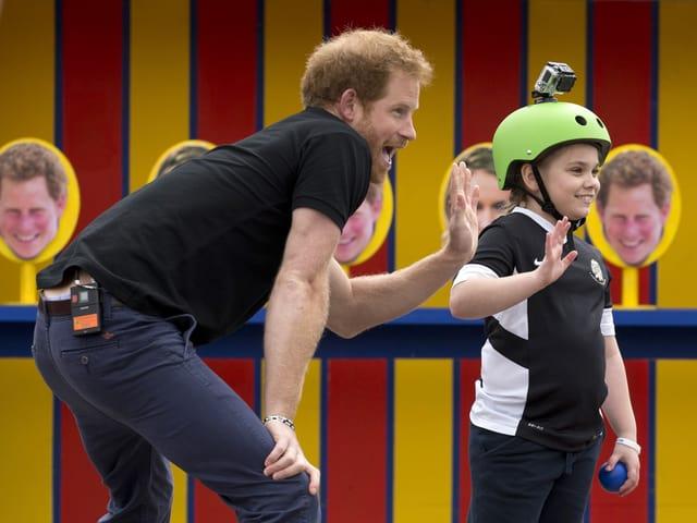Prinz Harry winkt mit einem Mädchen in die Kamera