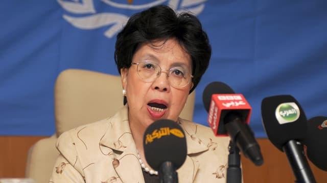Asiatische Frau mit Brille spricht in drei Mikrophone.
