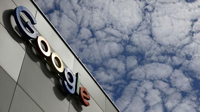 An einer grauen Gebäudewand hängt das Logo von Google.