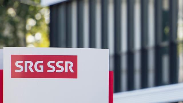 Il logo da la SSR sin ina tabla davant in bajetg da la SSR.