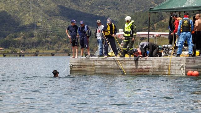 Taucher im Wasser, Hilfskräfte daneben.