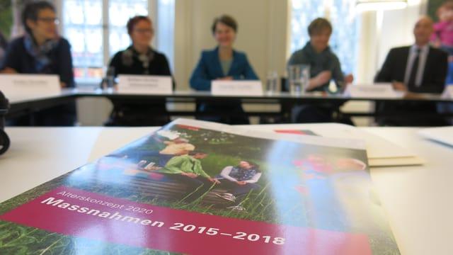 Eine Broschüre im Vordergrund, im Hintergrund unscharf fünf Personen.