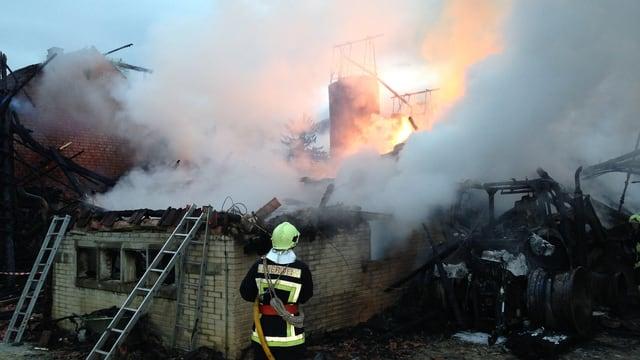 Feuerwehrmann steht vor der zerstörten Scheune.