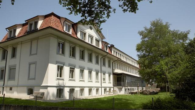 Spital Riggisberg, Altbau, besonnt, Rasen und Bäume.