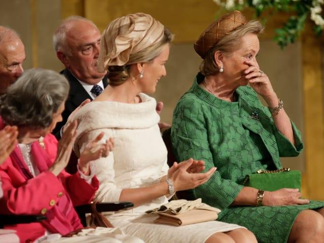 Paola wischt sich eine Träne ab, daneben sitzt Mathilde