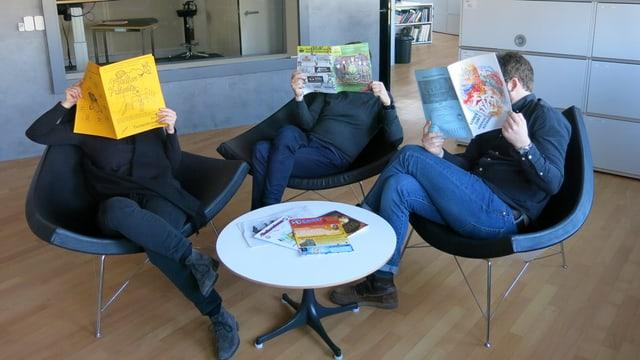 Drei Leute sitzen in Sesseln vor einem Salontisch und schauen in Fasnachtszeitungen.