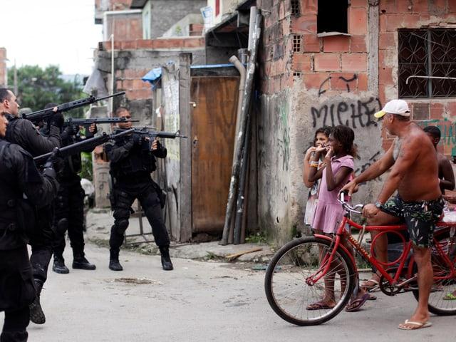 Sicherheitskräfte zielen mit ihren Waffen auf Favela-Bewohner.