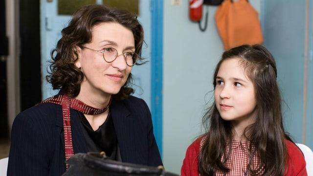 Frau mit Brille neben einem Mädchen in einem Schulzimmer