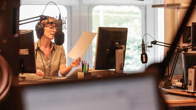 Eine Redaktorin steht im Sendestudio vor einem Mikrofon.