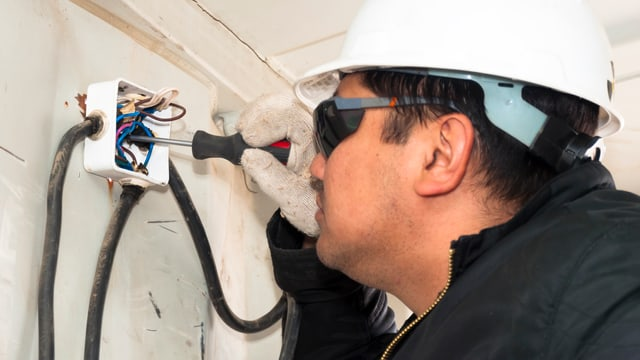 Ein Elektro-Installateur mit weissem Helm prüft die Kabel einer Steckose