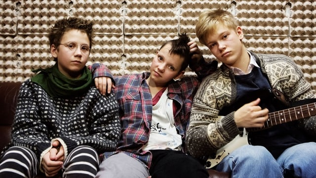 Drei Jugendliche mit Punkfrisuren sitzen auf einem Sofa.