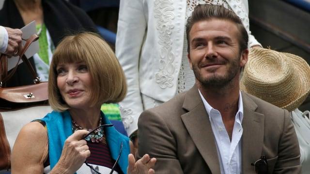 Anna Wintour (links) und David Beckham (rechts) sitzen nebeneinander und lächeln.