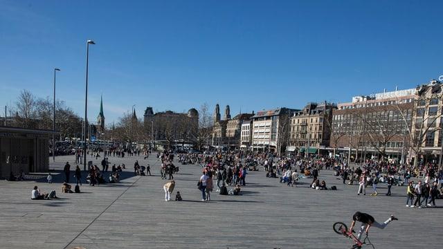 Menschen flanieren an einem schönen Tag auf dem Sechseläutenplatz
