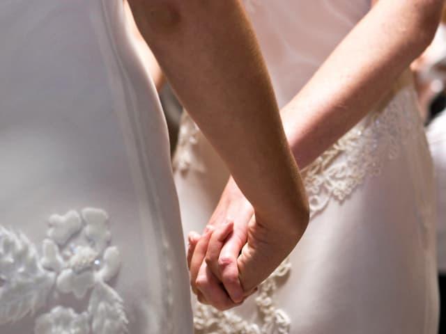 Die Hände von zwei weiss gekleideten Frauen, die sich halten.