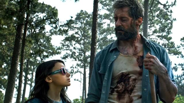 Ein Mädchen mit Sonnenbrille schaut hoch zu einem Mann, der mehrere Wunden hat