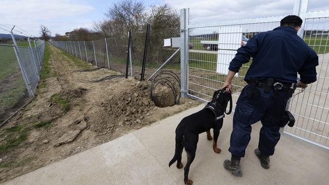 Im Vordergrund ein Wachmann mit Hund vor einem Gittertor, der Blick geht in den Zwischeraum zwischen zwei hohen Maschendrahtzäunen, der eine davon auf der Krone mit Stacheldraht bewehrt.