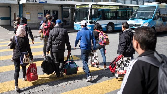 Flüchtlinge gehen über einen Fussgängerstreifen