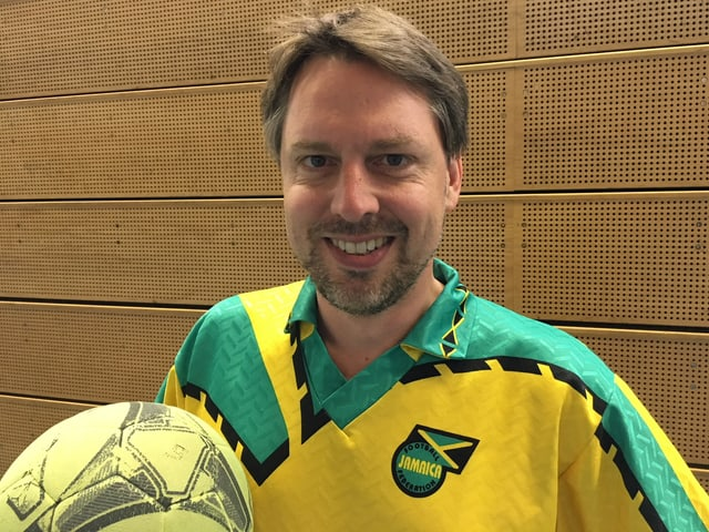 Ein Mann im Fussball-Trikot mit Ball.